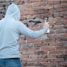 remaja melakukan vandalisme dengan mencoret dinding